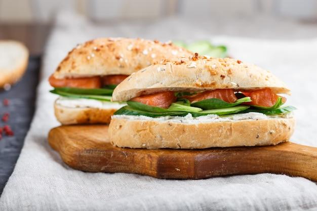 Wędzone łososie kanapki z ogórkiem i szpinakiem na desce na tle bielizny.