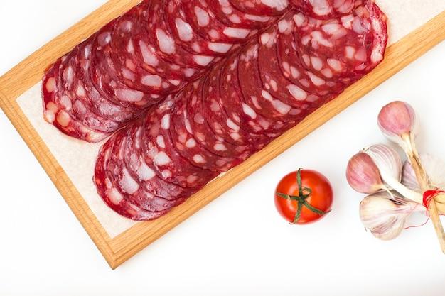 Wędzone mięso na desce do krojenia. pomidor i pęczek czosnku na białym tle