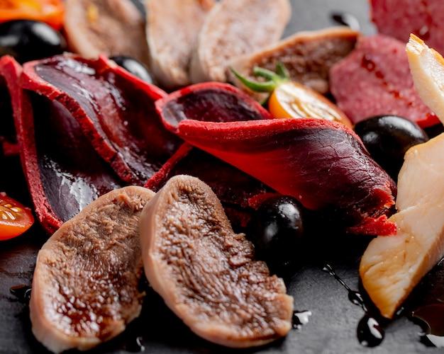 Wędzone mięso podawane z oliwkami i pomidorami