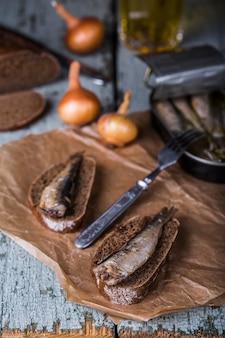 Wędzone szproty z chlebem żytnim na drewnianym tle