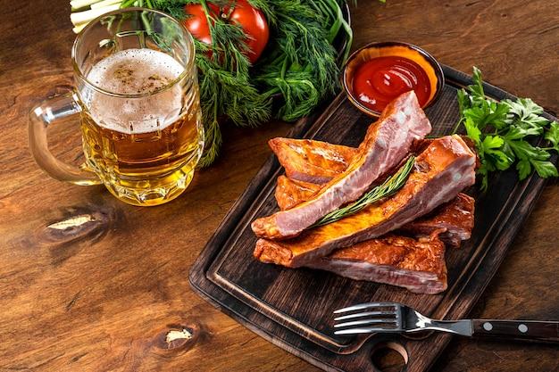 Wędzone żeberka wieprzowe z keczupem na desce do krojenia i szklanką jasnego piwa na podłoże drewniane
