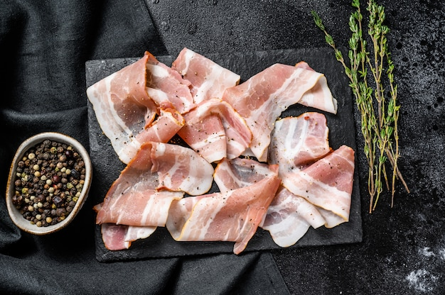 Wędzony boczek wieprzowy z pieprzem i tymiankiem. organiczne surowe mięso. widok z góry