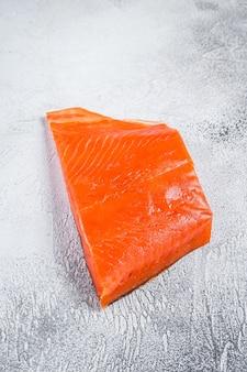 Wędzony filet z łososia na drewnianym stole. białe tło. widok z góry.