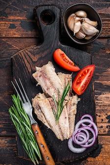 Wędzony filet z ryby sardynka na desce z ziołami