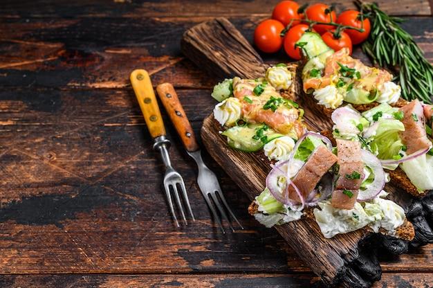 Wędzony łosoś i śledź kanapka z twarogiem i surówką na desce do krojenia