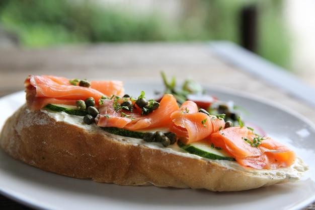 Wędzony łosoś na opiekanym chlebie ze świeżą śmietaną, cytryną i surówką