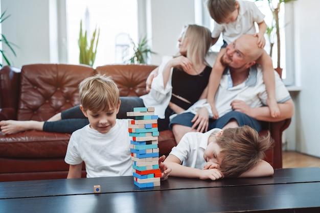 Weekend szczęśliwej rodziny kaukaski w nowoczesnym mieszkaniu. dwóch małych chłopców gra w grę jenga, rywalizując o to, kto jest lepszy.