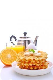 Weekendowe śniadanie: gofry z bananem ozdobione miętą, jajkiem, sokiem pomarańczowym.