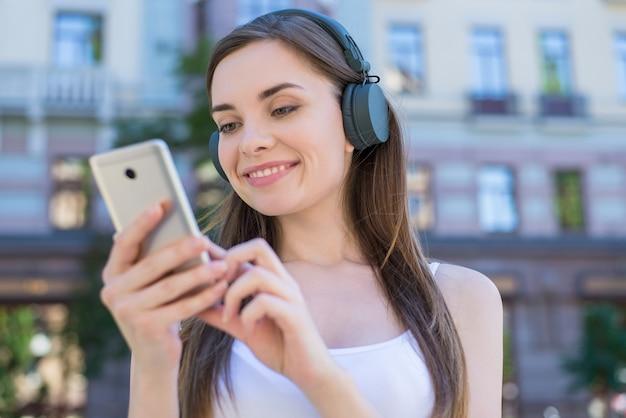 Weekendowe wakacje relaks reszta koncepcji dźwięku studenta. zbliżenie portret wesoły marzycielski zadowolony całkiem marzycielski pokojowy ona jej pani trzymając telefon w ręce, wybierając pobieranie piosenki