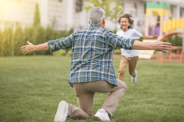 Weekendowy tata. chłopiec biegnący do swojego taty i wyglądający na szczęśliwego