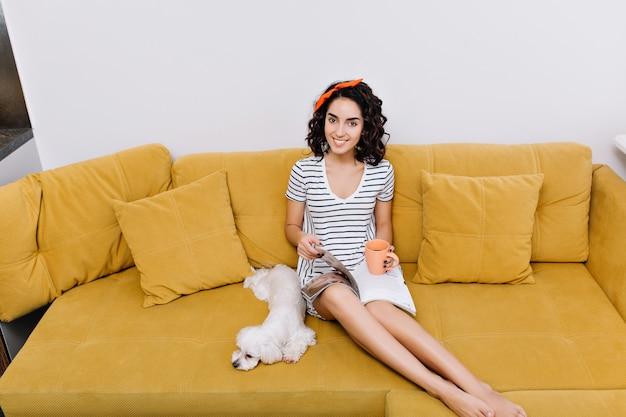 Weekendy, czas wolny niesamowitej, ładnej młodej kobiety z brunetką ściętymi kręconymi włosami uśmiechającej się na pomarańczowej kanapie w salonie. relaks z psem, czytanie gazet, dom