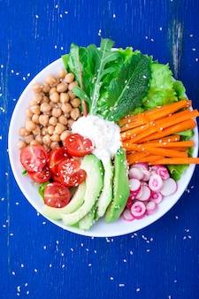 Weganinu buddha puchar na błękitny drewnianym. miska z marchewką, sałatą, pomidorami cherry, rzodkiewką, awokado i ciecierzycą. wegetariańska, zdrowa, detox koncepcja żywności. widok z góry.