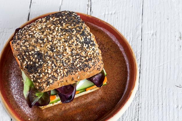 Weganinu hamburger z świeżymi warzywami na nieociosanym tle