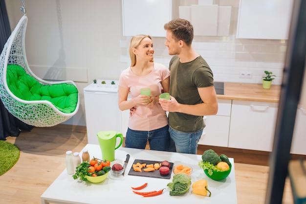 Wegańska kochająca para trzyma świeże napoje detoksykacyjne podczas gotowania surowych warzyw w kuchni