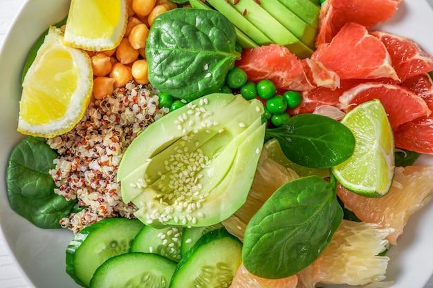 Wegańska koncepcja jedzenia: komosa ryżowa z awokado, ogórkami, zielonym groszkiem, ciecierzycą, szpinakiem i owocami cytrusowymi. widok z góry.