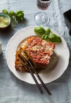 Wegańska lasagne z soczewicą i zielonym groszkiem w blasze do pieczenia na stole z niebieskim lnianym obrusem. i czerwone wino w kieliszkach