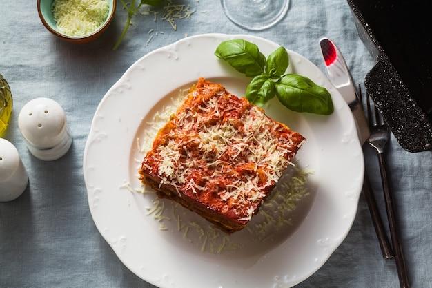Wegańska lasagne z soczewicą i zielonym groszkiem w blasze do pieczenia na stole z niebieskim lnianym obrusem.