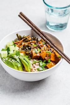 Wegańska miska ahi poke z tofu, ryżem, wodorostami, awokado i ogórkiem na białym tle