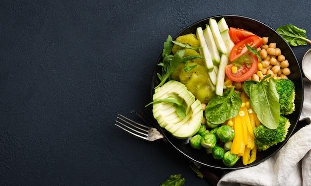 Wegańska miska buddy. koncepcja dietetyka zdrowej żywności. zdrowy wegetariański obiad warzywny z ciecierzycy, brokułów, pieprzu, pomidorów, szpinaku, rukoli i awokado. widok z góry