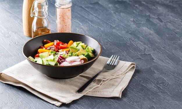 Wegańska miska buddy. miska ze świeżymi surowymi warzywami - pomidorkami koktajlowymi, ogórkiem, rzodkiewką, awokado, sałatą romano, frisse i ridicho. zdrowa sałatka wegetariańska. dieta ketogeniczna.
