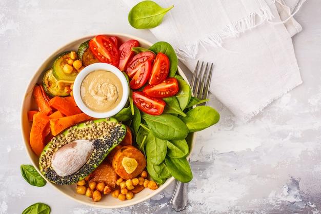 Wegańska miska buddy z pieczonymi warzywami, ciecierzycą, dressingiem z awokado i tahini na białej przestrzeni, widok z góry, miejsce na kopię.