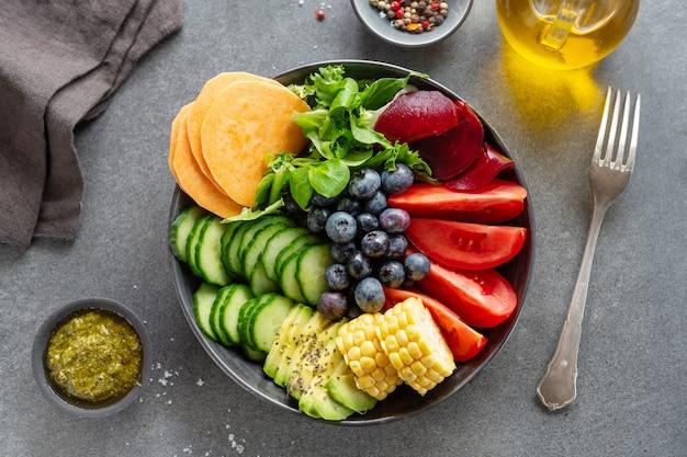 Wegańska miska buddy z warzywami i owocami serwowana w misce na szarym tle. zbliżenie
