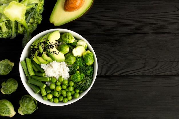 Wegańska miska poke z białym ryżem i zielonymi warzywami w białej misce na czarnym drewnie.