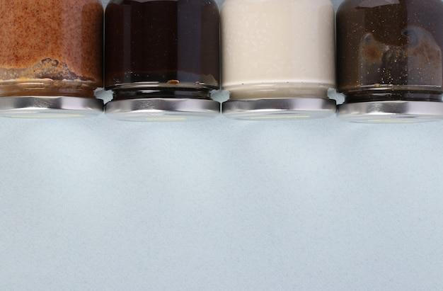 Wegańska organiczna pasta z nasion lnu, ostropestu, orzeszków ziemnych i kokosa w szklanych słoikach na jasnoniebieskim tle, urbech. zdrowy produkt spożywczy. miejsce na tekst