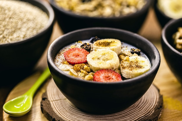 Wegańska owsianka z quinoa, truskawka, banany, mielone orzechy i posypany cynamonem. deser bez laktozy bez mleka