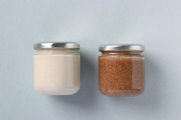 Wegańska pasta organiczna z orzeszków ziemnych i kokosa w szklanych słoikach na jasnoniebieskim tle. kuchnia dagestanu. zdrowy produkt spożywczy, urbech. widok z góry