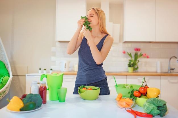 Wegańska piękna blondynka cieszy się zapachem organicznej pietruszki przed gotowaniem w kuchni. jedzenie wegetariańskie. zdrowe jedzenie. dieta wegańska