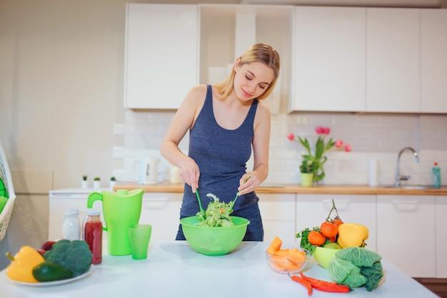 Wegańska piękna blondynki kobieta gotuje wyśmienicie sałatki w kuchni. jedzenie wegetariańskie. zdrowe odżywianie. dieta wegańska