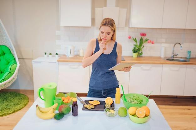Wegańska piękna blondynki kobieta szuka przepisu w tablecie na gotowanie organicznych owoców w kuchni. zdrowe jedzenie. detoksykacja diety