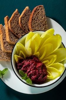 Wegańska przekąska z pastą z pieczonych buraków i pistacji oraz liśćmi endywii belgijskiej