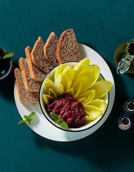 Wegańska przekąska z pasty z pieczonych buraków i pistacji oraz liści endywii belgijskiej z pieczywem pełnoziarnistym na stole