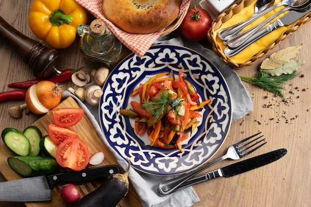 Wegańska sałatka jarzynowa z bakłażana, marchewki, papryki słodkiej, ogórka i pomidora doprawiona olejem na talerzu z tradycyjnym uzbeckim