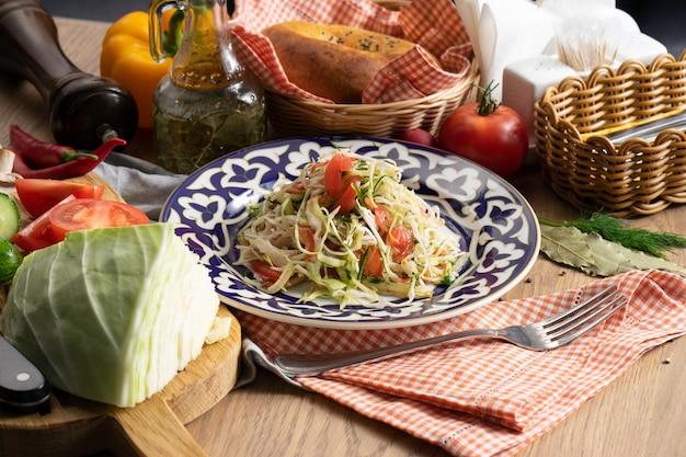 Wegańska sałatka jarzynowa z kapusty, ogórka i pomidorów doprawiona olejem na talerzu z tradycyjnym uzbeckim