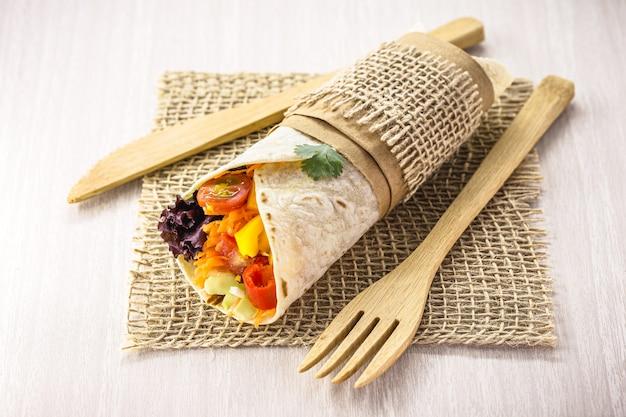 Wegańska tortilla wrap, wegetariańska rolka z grillowanymi warzywami, papryką, soczewicą, pomidorami i kapustą, na rustykalnej drewnianej powierzchni