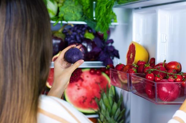 Wegańska wegetariańska kobieta biorąca fioletową zdrową śliwkę przeciwutleniającą do jedzenia po targu w pobliżu lodówki z kolorowymi warzywami, surowym sokiem i owocami: grejpfrutem, pomidorami, arbuzem, ananasem, figą