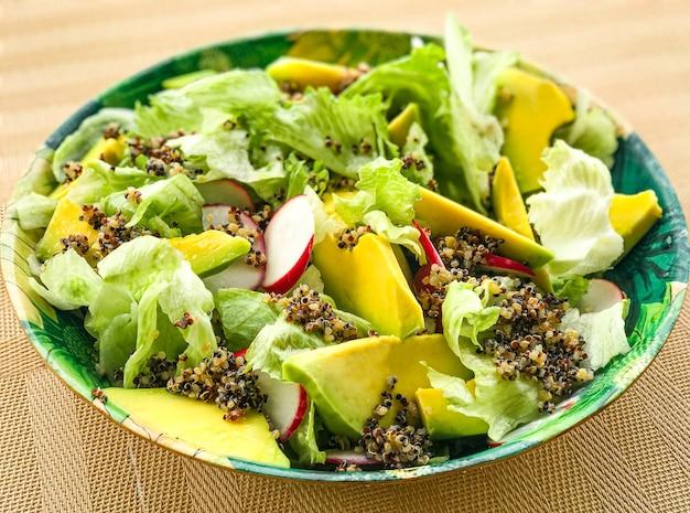 Wegańska zielona sałatka z awokado, rzodkiewką, sałatą i komosą ryżową.