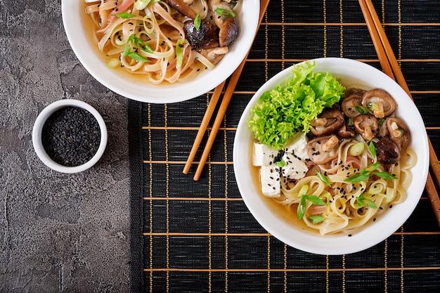 Wegańska zupa z makaronem z serem tofu, grzybami shiitake i sałatą w białej misce. azjatyckie jedzenie. widok z góry. leżał płasko