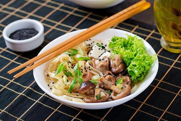 Wegańska zupa z makaronem z serem tofu, grzybami shiitake i sałatą w białej misce. azjatyckie jedzenie.