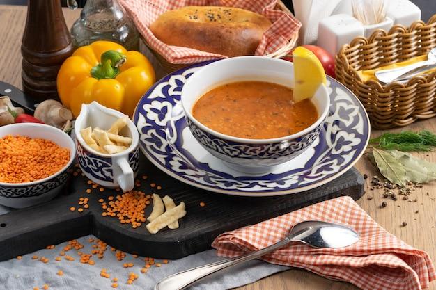 Wegańska zupa z soczewicy z frytkami z cytryny i pszenicy w talerzu z tradycyjnym uzbeckim