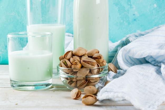 Wegański alternatywny jedzenie, pistacjowy nie nabiału mleko na bławym tle, kopii przestrzeń