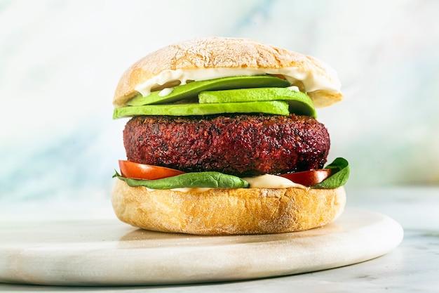 Wegański burger bez mięsa z awokado, pomidorami i szpinakiem na stole i czerwonym winem w kieliszku