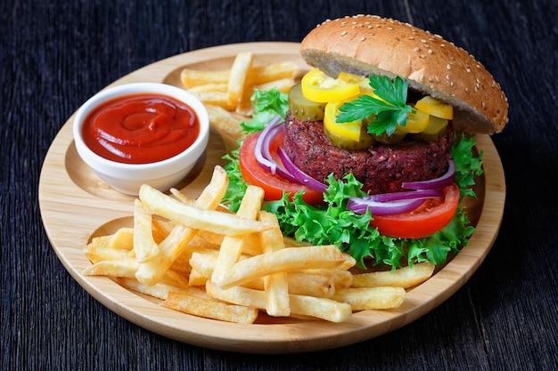 Wegański burger buraczany z piklami świeża sałata, pomidory, czerwona cebula, frytki, ketchup na bambusowym talerzu na ciemnym drewnianym stole, widok z góry, zbliżenie