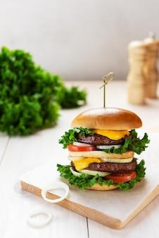 Wegański burger na drewnianej desce na jasnym tle