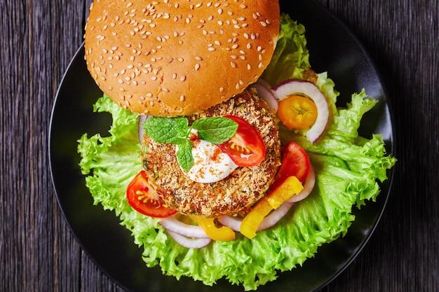 Wegański burger wegetariański z ciecierzycy ze świeżo upieczoną bułką zwieńczoną sezamem i sałatką na czarnym talerzu, płasko ułożony, zbliżenie, makro