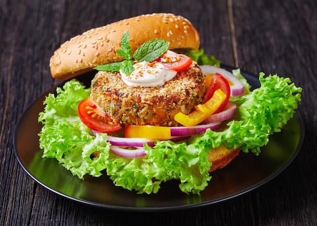 Wegański burger wegetariański z ciecierzycy ze świeżo upieczoną bułką zwieńczoną sezamem i sałatką na czarnym talerzu, widok krajobrazowy, zbliżenie, makro