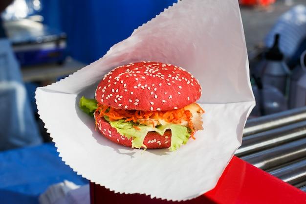 Wegański burger z czerwonej bułki w papierze
